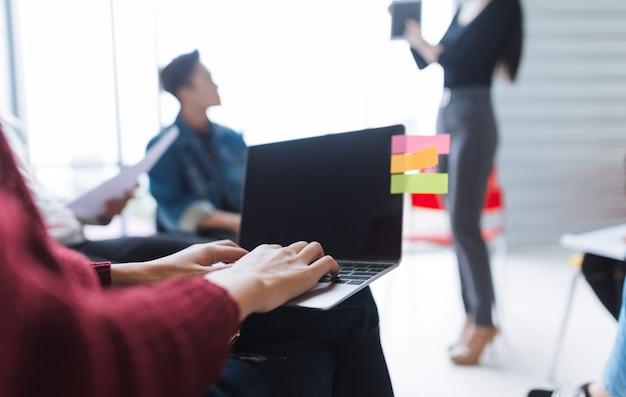 Hombres de negocios que trabajan usando el ordenador portátil en sala de reunión.