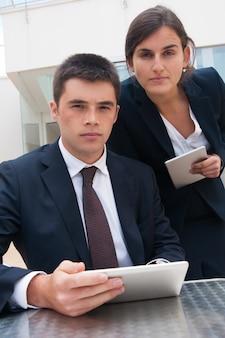 Hombres de negocios serios que presentan en la cámara y que sostienen las tabletas