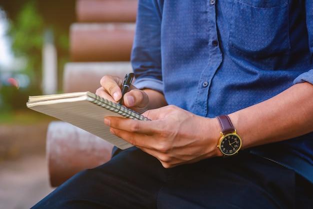 Los hombres de negocios se sientan y escriben libros en el parque.
