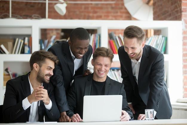 Hombres de negocios sonrientes multiétnicos en trajes que miran algo divertido en el ordenador portátil