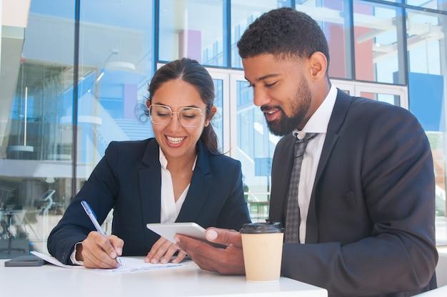 Hombres de negocios sonrientes que trabajan y que usan la tableta en café al aire libre