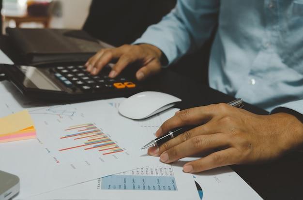 Los hombres de negocios sostienen la pluma y la calculadora para ver gráficos e informar el crecimiento de las ventas y el negocio.