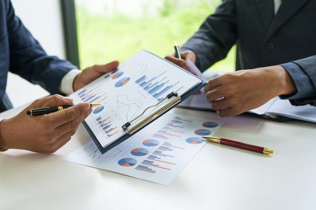 Los hombres de negocios y sus colegas están discutiendo las inversiones y los gráficos juntos en la oficina, el concepto de trabajo en equipo.