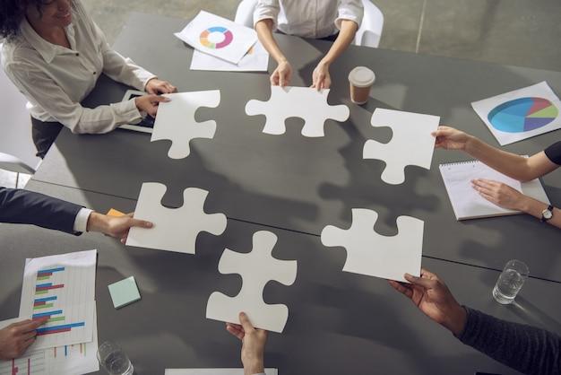 Hombres de negocios trabajando juntos para construir un rompecabezas. concepto de trabajo en equipo, asociación, integración y puesta en marcha.