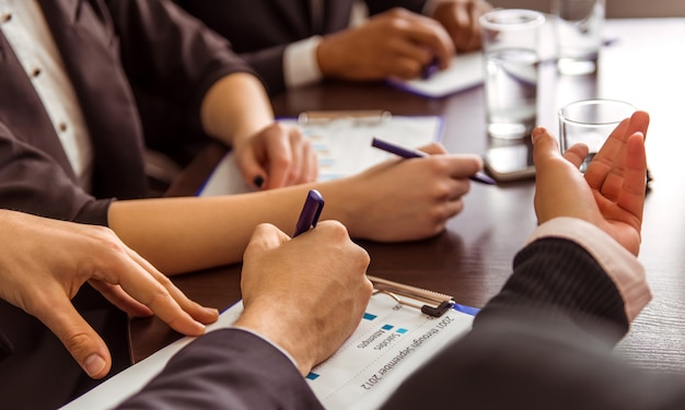 Los hombres de negocios en trajes firman papeles en oficina.