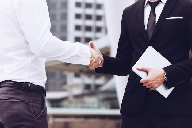 Los hombres de negocios unen sus manos en un negocio