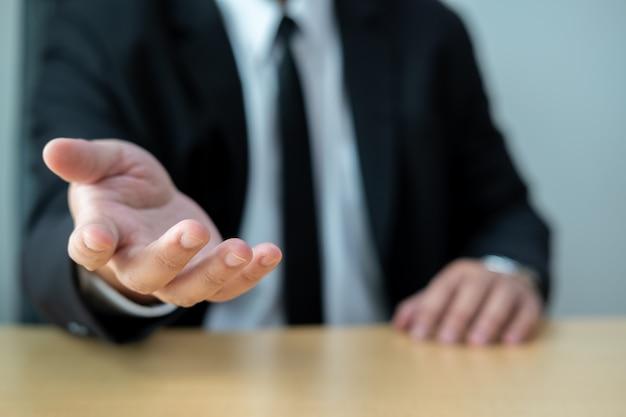Los hombres de negocios usan trajes sentados en escritorios y saludan a algunas personas