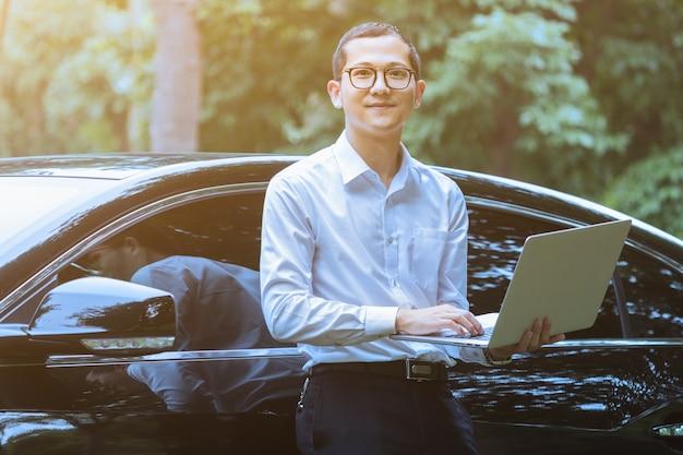 Los hombres de negocios utilizan laptops junto a vehículos al aire libre
