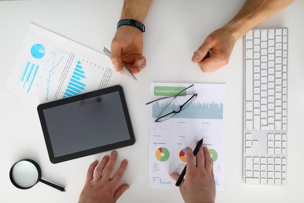 Los hombres de negocios verifican y analizan el informe de ganancias