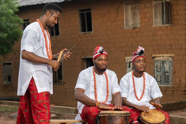 Hombres nigerianos tocando música tiro medio