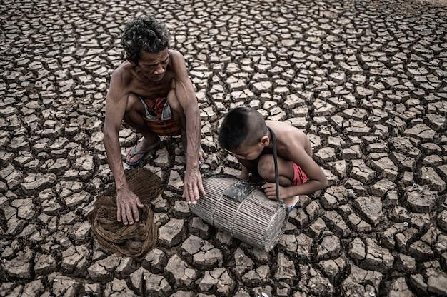 Los hombres y los niños mayores encuentran peces en tierra seca, el calentamiento global