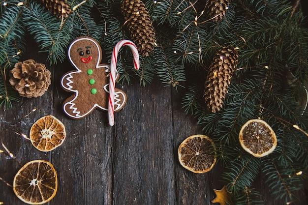 Hombres de pan de jengibre con los copos de nieve del bastón de caramelo que ponen en fondo de madera gris. composición de navidad o año nuevo. tarjeta de navidad.
