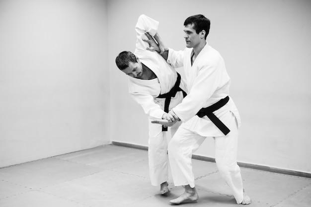 Hombres peleando en el entrenamiento de aikido en la escuela de artes marciales