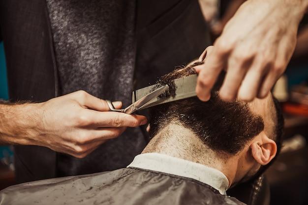 Hombres peluquero corta la barba.