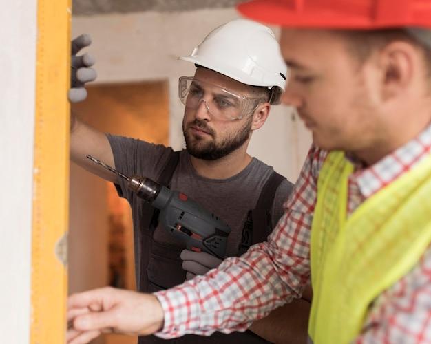 Hombres de primer plano trabajando con taladro