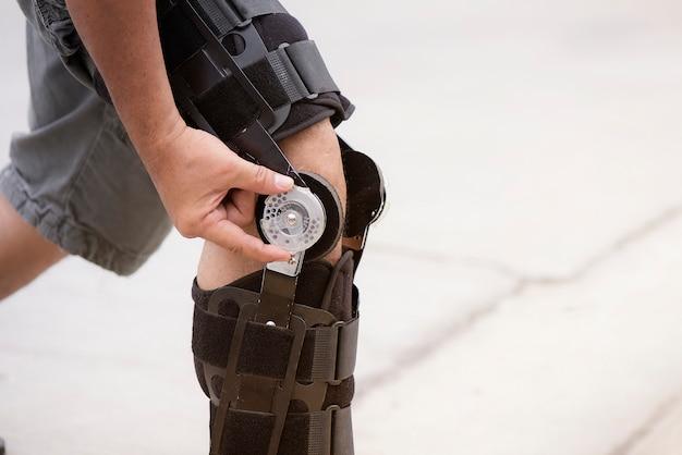 Los hombres que llevan un cinturón de soporte de rodilla concepto de cuidado para la osteoartritis