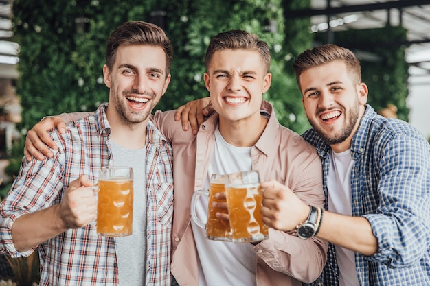 Los hombres se quedan en la terraza de verano y beben cervezas.