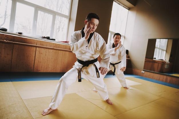Hombres con ropa blanca y cinturones negros entrenan en el gimnasio.