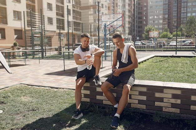 Los hombres en ropa deportiva descansan después de entrenar en un parque