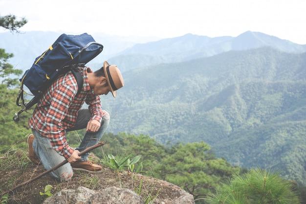 Los hombres se sientan y miran montañas en los bosques tropicales con mochilas en el bosque. aventura, viajar, escalar.
