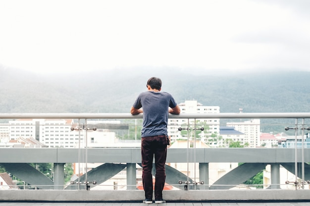 Los hombres solitarios están mirando la ciudad y la puesta de sol