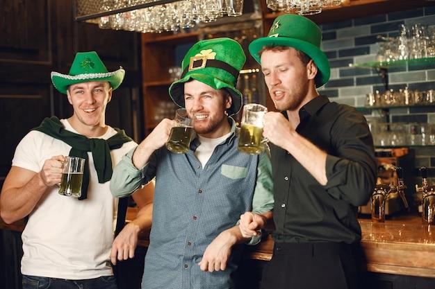 Hombres con sombreros verdes. los amigos celebran el día de san patricio. celebración en un pub.