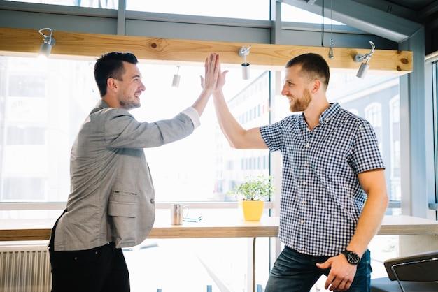 Hombres sonrientes dando hight-five en la oficina