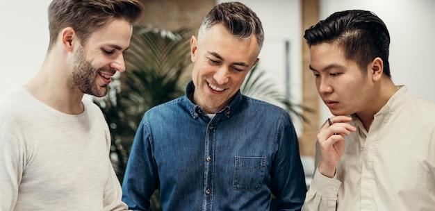 Hombres sonrientes hablando de un proyecto en la oficina