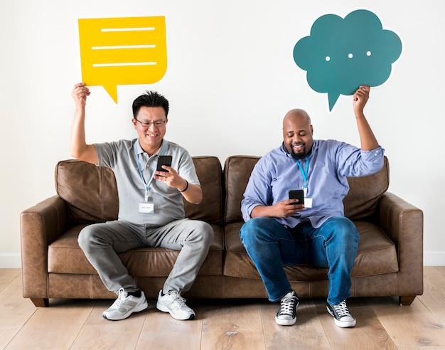 Hombres sosteniendo cajas de mensajes y trabajando en el móvil.