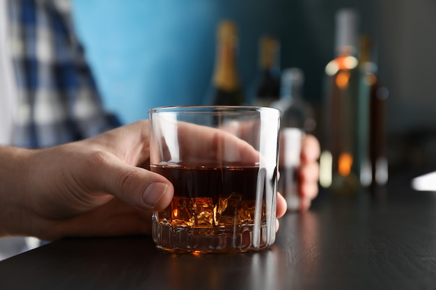Hombres sosteniendo copas de whisky en el bar.