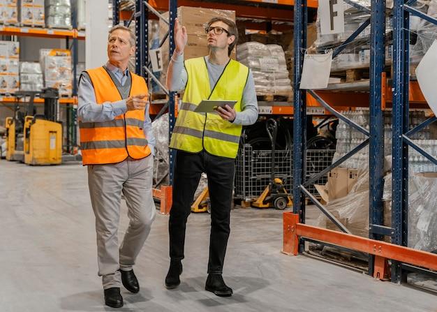 Hombres con tableta de trabajo logístico.