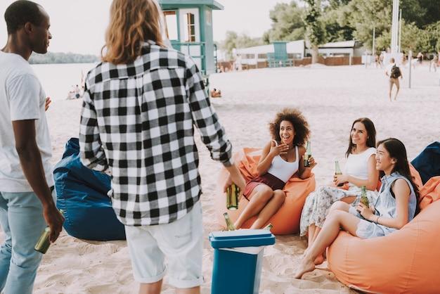Los hombres tienen cerveza en el refrigerador para la fiesta en la playa