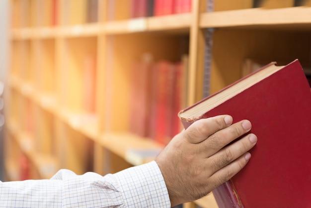 Los hombres tienen libros leídos en la biblioteca del campus.