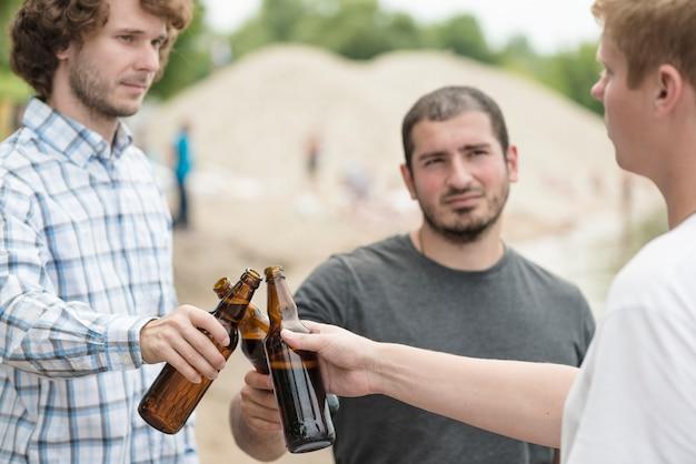 Hombres tintinean botellas en la playa
