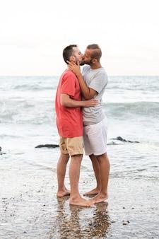 Hombres de tiro completo besándose en la orilla