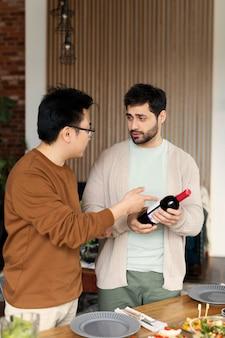 Hombres de tiro medio con botella de vino