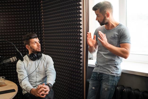 Hombres de tiro medio en la estación de radio