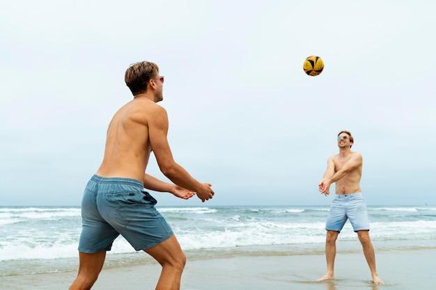 Hombres de tiro medio jugando voleibol