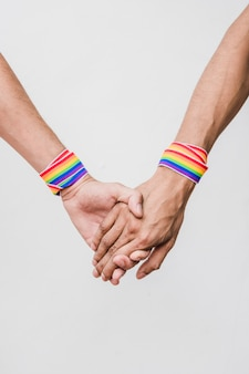 Hombres tomados de las manos con cintas en colores lgbt.