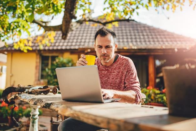 Hombres tomando café y usando una computadora portátil en el patio trasero