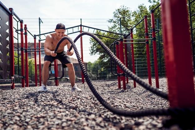 Los hombres trabajan duro con la cuerda, entrenamiento funcional