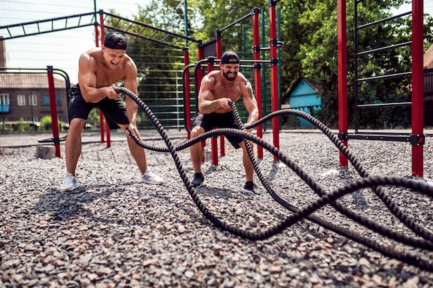 Los hombres trabajan duro con una cuerda en el patio del gimnasio de la calle. entrenamiento al aire libre. concepto de fitness, deporte, ejercicio, entrenamiento y estilo de vida.