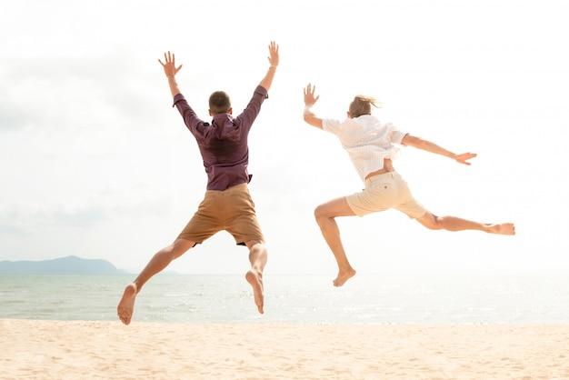 Hombres turísticos felices enérgicos jovenes que saltan en la playa