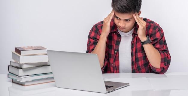 Los hombres usan computadoras portátiles en la oficina y están estresados.