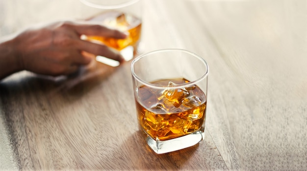 Los hombres y los vasos de whisky beben bebidas alcohólicas junto con amigos mientras están en la barra del bar