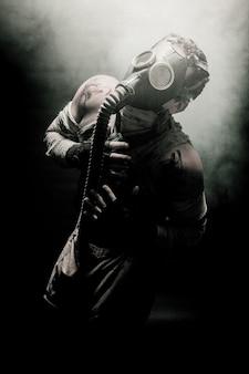 Hombres vendados con máscara de gas rodeados de humo y mirando al cielo, soldado de supervivencia después del apocalipsis.