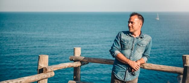 Hombres vestidos con camisa vaquera de pie junto al mar y contemplando