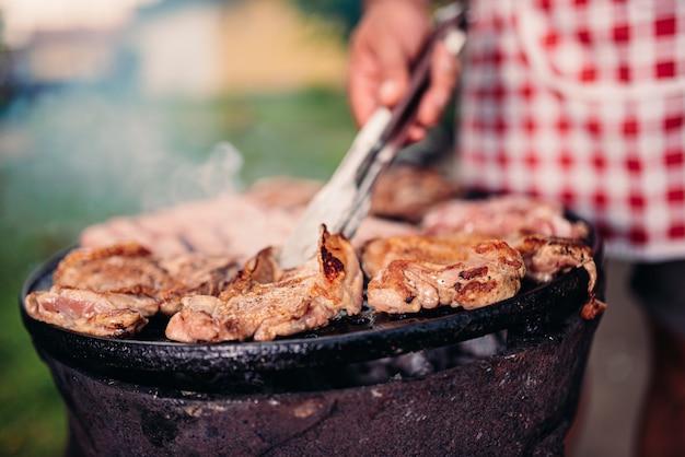 Hombres vestidos con delantal asando carne de pollo