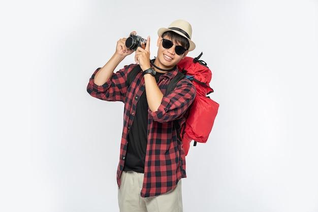 Hombres vestidos para viajar, con gafas y sombreros llevando un bolso y llevando una cámara
