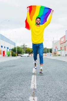 Homosexual corriendo por la carretera con bandera lgbt sobre la cabeza